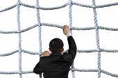 Businessman Climbing Crisscross Rope Net Isolated On White