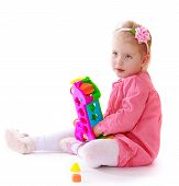 Little girl sitting on the floor and plays with an interesting t