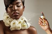 image of black woman spa  - beautiful black woman with flowers on her neck and a hand with a perfume bottle - JPG