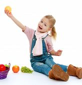 Little girl holding her at arm's length apple.