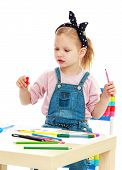Little girl draws pencils sitting at the table.
