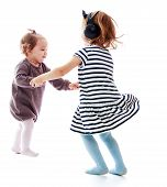 Two girls holding hands sisters dance in a circle.