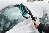 Man Cleans Car From Snow With Brush