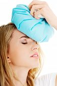 Beautiful woman with ice bag, having headache.