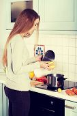 Beautiful young woman standing in the kitchen and preparing food.