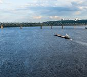 pic of barge  - The barge floating in the blue Dnieper waters against the summer Kyiv landscape - JPG