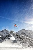 Red Helicopter In Flight In Winter Alps With Snow Powder