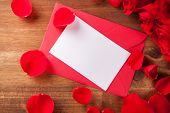 Bouquet of roses with blank paper with envelope on wooden desk