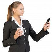 Businesswoman holding mug and using mobile phone