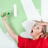 Woman With Open Mouth With Paint Roller In Hand
