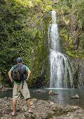 Man hiking to a beautiful tropical waterfall