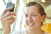 stock photo of young adult  - a young woman is watching at phone - JPG