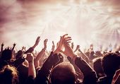 Vintage style photo of a crowd, happy people enjoying rock concert, raised up hands and clapping of  poster