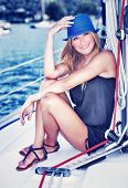 Pretty woman relaxing on luxury sailboat, sitting on the deck and enjoying leisure time in the sea, happy summer vacation concept