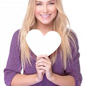 Closeup soft focus portrait of beautiful blond girl holding in hands paper heart isolated on white background, healthy lifestyle or Valentine day celebration