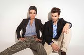 Attractive young fashion woman sitting on the floor with her legs apart while her boyfriend is sitting next to her, looking down.