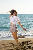 foto of beachfront  - Full Length Shot of Happy Young Female Jumping at the Beachfront While Looking at the Camera - JPG