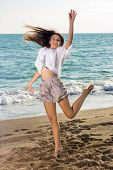 Young Woman In Funny Jump Shot At The Seaside
