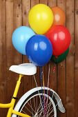 Yellow bicycle with balloons on wooden wall background