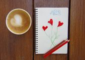 cup of coffee with cookie and drawing, buttons shaped heart