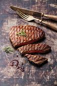 Sliced Medium Rare Grilled Beef Steak Ribeye On Dark Metal Background