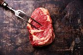 Raw Fresh Meat Ribeye Steak And Meat Fork On Dark Metal Background
