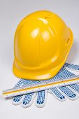 Close Up Of Builder's Tools - Helmet, Work Gloves And Ruler Over White