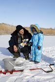 picture of grandpa  - 4 year old boy on winter fishing with grandpa