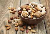 stock photo of mixed nut  - Mixed nuts in a bowl on a wooden background - JPG