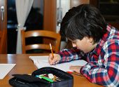 Young Boy Writes On His Notebook