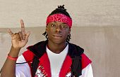 picture of good-looker  - Cool Black Teen displaying the universal sign for rock and roll - JPG