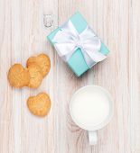 Cup of milk, heart shaped cookies and gift box on white wooden table