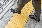 Man Legs Are Crossing The Yellow Line On The Train Station