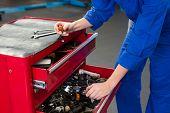 Mechanic looking for tool in drawers at the repair garage