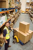 Worker with trolley of boxes smiling at camera in a large warehouse