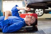 Mechanic lying and looking under car at the repair garage