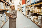 Businesswoman smiling while writing on a clipboard in a large warehouse