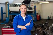 Mechanic looking at camera holding wrench at the repair garage