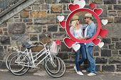 Hip young couple hugging by brick wall with their bikes against hearts