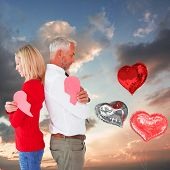Couple holding two halves of broken heart against blue and orange sky with clouds