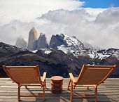 Two comfortable wooden deck chairs are on the platform overlooking the cliffs Torres del Paine