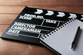 picture of clapper board  - Movie clapper with notebook and pen on wooden background - JPG