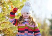Child And Christmas Ball Outdoors In Winter Sunny Day