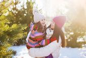 Winter And People Concept - Mother And Child Having Fun Playing In Sunny Winter Day