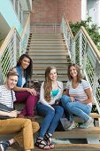 Smiling students sitting on steps at the university