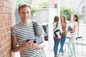 Handsome student smiling and holding tablet at the university