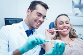 pic of false teeth  - Male dentist teaching woman how to brush teeth in the dentists chair - JPG