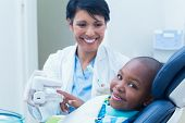 pic of prosthesis  - Female dentist showing young boy prosthesis teeth - JPG
