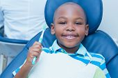picture of toothbrush  - Portrait of young boy holding toothbrush in the dentists chair - JPG