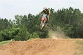 stock photo of moto-x  - Person jumping a jump on a motorcross bike 